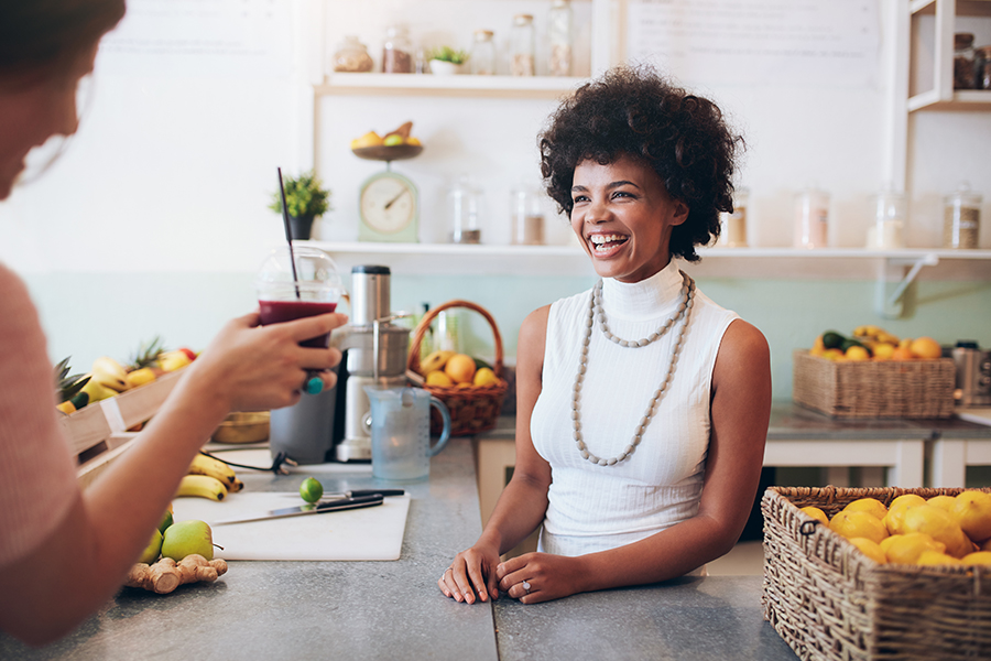 Business Insurance - Smiling Young Woman Talking to Customer From Her Small Business Juice Bar